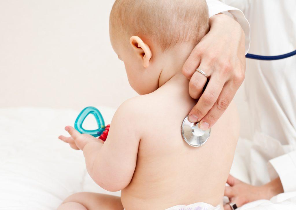 """Médico consultando com estetoscópio um bebê, ilustrando o artigo """"Cólica em recém-nascido"""""""